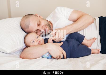 Portrait de l'âge moyen woman in white t-shirt au lit avec bébé nouveau-né fils tenant ses mains, les doigts de la petite enfance parents con collage