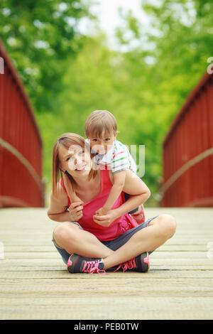 Portrait de mère et fils, assis sur le pont de bois et s'étreindre dans la forêt campagne village sourire et rire, concept de famille heureuse Banque D'Images