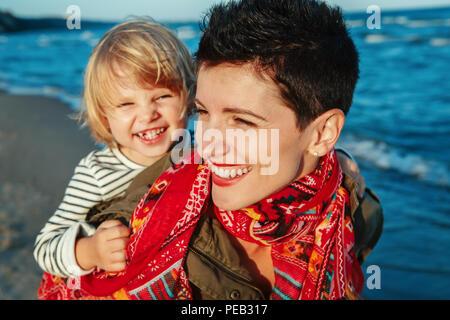 Closeup portrait de groupe de white Caucasian mother and daughter hugging baby girl smiling rire à l'exécution sur Océan mer plage au coucher du soleil en plein air Banque D'Images