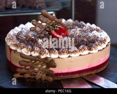 Tarte au fromage aux framboises, décorées avec des fraises fraîches, sur fond noir Banque D'Images