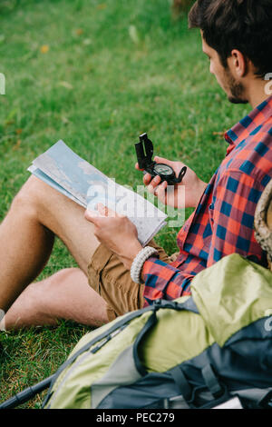 Cropped shot of man holding la carte et la boussole en étant assis sur l'herbe