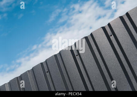Plaque de métal brun contre blue cloudy sky. D'évitement. Surface sans couture d'acier galvanisé. Bâtiment industriel mur fait de feuille de métal ondulé, texture de fond photo Banque D'Images