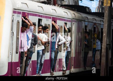 Les passagers des trains de banlieue de Mumbai porte sur un train de chemin de fer à la gare de Bandra à Mumbai, Inde