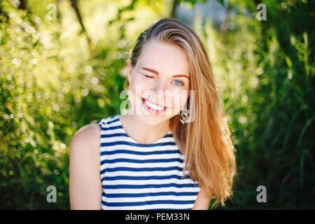 Beautiful smiling white Caucasian girl woman winking avec de longs cheveux blonds et des yeux bleus portant des T-shirt à rayures à l'extérieur en été entre parc f vert