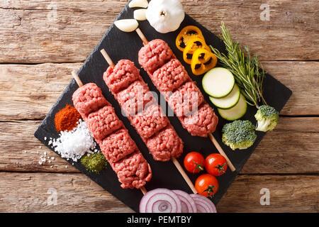 Kebab de boeuf haché cru avec des ingrédients et des légumes sur la table. Haut horizontale Vue de dessus Banque D'Images