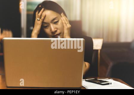 Femme d'affaires à la recherche de travail stress sur ordinateur dans les heures supplémentaires, Banque D'Images