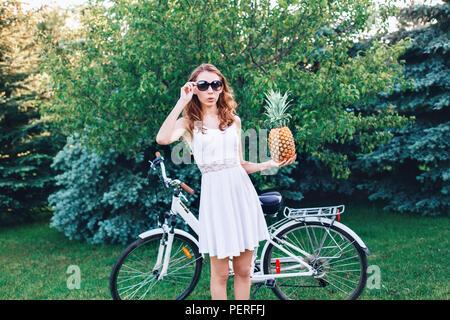 Portrait of young beautiful white Caucasian woman girl à lunettes de soleil, de fruits ananas holding, debout avec le vélo dans le parc à l'extérieur sur les jours de l'été, moder