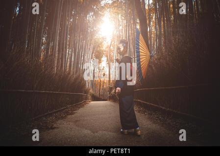 Belle japonaise hauts femme marche dans la forêt de bambous Banque D'Images