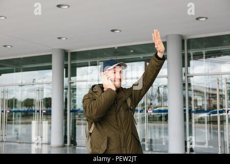 Un jeune homme à l'aéroport touristique ou près d'un centre commercial ou un poste, un taxi ou les discussions sur un téléphone cellulaire ou communique avec des amis à l'aide d'un téléphone mobile. Banque D'Images