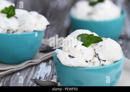 Trois boules de pâte à biscuits aux pépites de chocolat de la crème glacée. L'extrême profondeur de champ avec focus sélectif sur la cuvette à l'avant. Banque D'Images