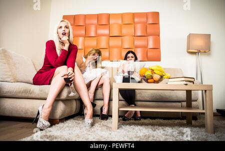 Trois amis de regarder la télévision sur le canapé Banque D'Images