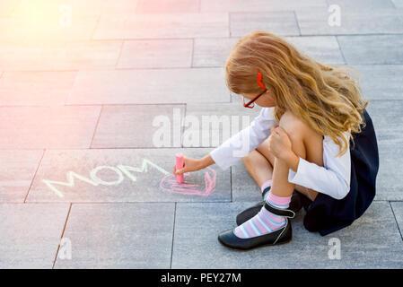 Un peu cute schoolgirl dessine une craie de couleur sur le trottoir de l'amour maman. Après l'école, à l'extérieur Banque D'Images