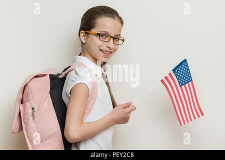 Enfant de l'école avec un sac à dos tient le drapeau américain, l'arrière-plan lumineux mur dans l'école. Banque D'Images