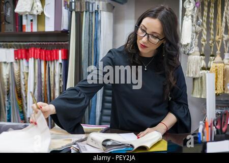 Femme est propriétaire d'un magasin de tissus d'intérieur et décoration travaille avec des échantillons de matériaux. Accueil Petites entreprises de fabrication de textiles Banque D'Images