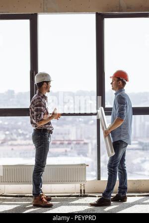 Les travailleurs de la construction travaillent ensemble sur le plan d'affaires en chambre avec fenêtre panoramique vue côté shot. Banque D'Images