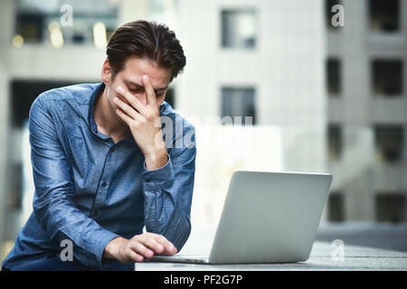Après l'échec du projet stressed businessman. Jeune homme confus frustrés par problème en ligne. Banque D'Images
