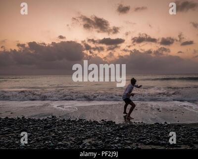 Parution d'une photo du modèle adolescent skimming stones au crépuscule sur la plage Banque D'Images