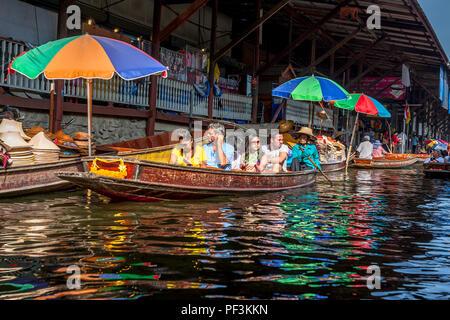 Les touristes flottent dans un bateau au marché flottant en Thaïlande. damnoen, Thaïlande, 22 novembre 2014. Dans un bateau touristique avec reflecitons couleur sur l'eau. Banque D'Images