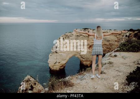 Jeune femme touriste jouit d'une vue magnifique sur l'océan Atlantique et le paysage de la côte du Portugal et soulève ses bras vers le haut montrant ho Banque D'Images
