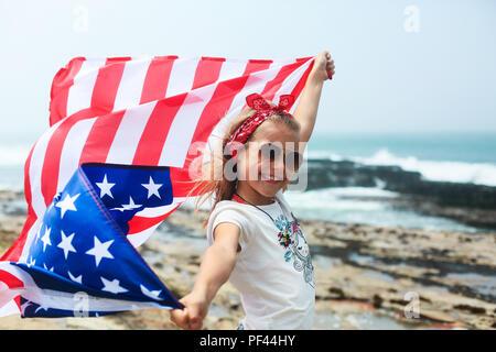 Un petit sourire fille patriotique est titulaire d'un drapeau américain célébrant le jour de l'indépendance Fête de l'USA le 4 juillet Banque D'Images