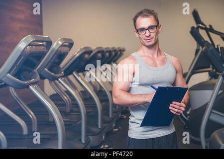 Femme travaillant dans une salle de fitness avec son entraîneur personnel Banque D'Images