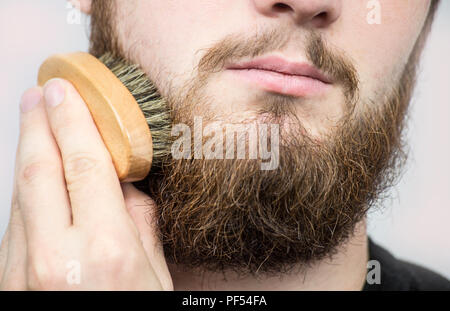 Main de coiffure brushing barbe. Salon de coiffure,client vue avant. Toilettage barbe Conseils aux débutants. Banque D'Images