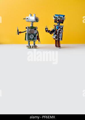 Des robots sur fond jaune. 4ème révolution industrielle concept d'automatisation. Technicien robotique avec tournevis, creative design cyborg les jouets. Maintenance réparation fix concept. copy space Banque D'Images