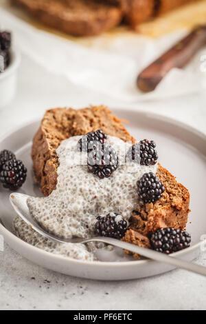 Vegan au chocolat Pain aux courgettes avec chia pudding et mûres, fond blanc. Concept de l'alimentation propre. Banque D'Images