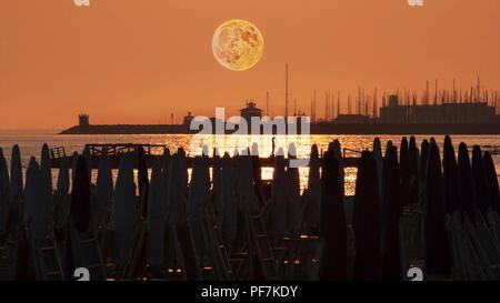 Belle pleine lune rouge au-dessus du port vu de la plage avec parasols Banque D'Images