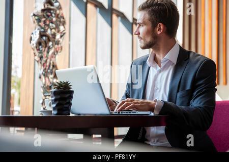 Young businessman working on laptop, assis dans le hall de l'attente de quelqu'un. Banque D'Images