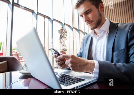 Homme d'affaires en costume noir à l'aide de téléphone intelligent et de travail sur ordinateur portable, la navigation sur internet et écrit sur papier au bureau de l'ordinateur portable moderne. L'homme travaillant sur les dispositifs de l'électronique avec copie espace Banque D'Images