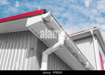 Gouttières blanc sur une maison au toit rouge sur fond de ciel bleu. Système de gouttières en plastique. L'extérieur du tuyau de drainage chêneaux Banque D'Images