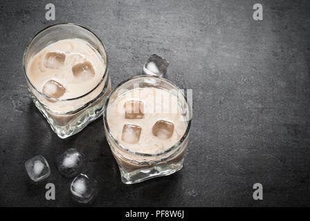 Boisson à la crème irlandaise dans les verres avec de la glace sur le noir. Banque D'Images