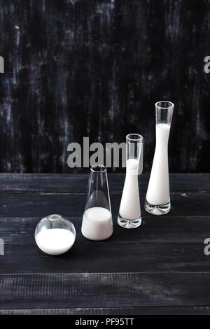 Composition diagonale de verre de différentes formes et tailles remplis avec du lait ou du yaourt sur un fond noir. Produits laitiers biologiques naturelles. Banque D'Images