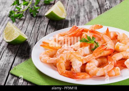 Queues de crevettes bouillies king sur un plat blanc avec persil et tranches de lime sur une vieille table rustique, close-up, studio lights Banque D'Images