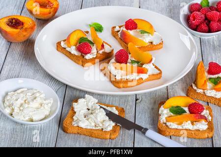 Petit-déjeuner frais d'été en bonne santé - toasts avec fromage mascarpone, framboise, pêche et menthe, tranches de fromage à la crème dans des bols sur la vieille table blanche, close-up Banque D'Images