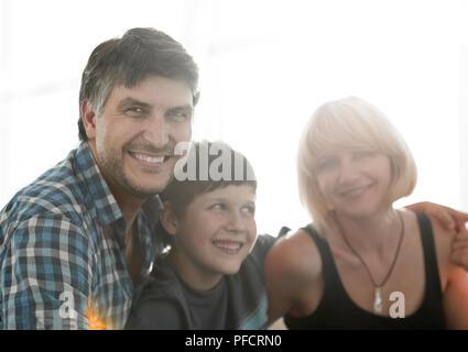 Les parents et leurs fils s'asseoir blottis dans le salon et souriant Banque D'Images
