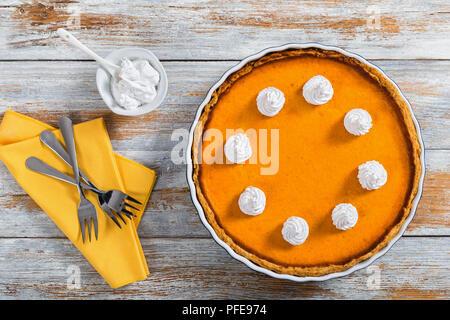 Ouvrir la citrouille orange vif délicieux gâteau dans le plat de cuisson décoré de crème fouettée, avec dessert fourchettes sur serviette et crème en saucière sur vieux tabl