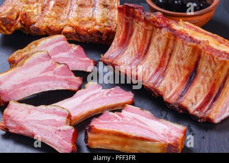 Côtes de porc fumé délicieux ensemble et les couper en tranches sur le plateau en pierre noir, vue de dessus, Close up Banque D'Images