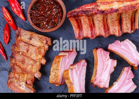 Côtes de porc fumé délicieux ensemble et les couper en tranches sur ardoise plateau avec la sauce barbecue et le piment fort, vue de dessus, close-up Banque D'Images