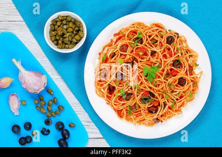 Les pâtes spaghetti à la sauce tomate, les câpres et les olives sur la plaque avec des ingrédients sur une planche à découper sur fond de bois, recette traditionnelle Italienne Banque D'Images