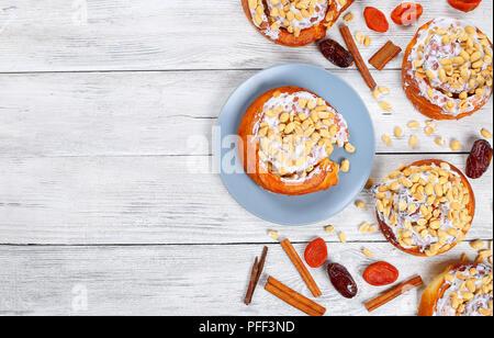 Délicieux faits maison fraîchement cuits au four à la cannelle garnies de l'arachide sur table en bois avec abricot sec, fruits séchés et des bâtons de cannelle date, voir fr Banque D'Images