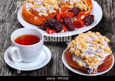 Délicieux faits maison fraîchement cuits au four à la cannelle garnies de l'arachide sur la plaque à l'abricot sec, fruits secs/ cup date avec plateau de table en bois, vue sur Banque D'Images