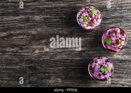 Dessert d'été de cassis et de ricotta mousse yogourt congelé saupoudrée de chocolat haché finement décoré de feuilles de menthe dans le verre tasses Banque D'Images