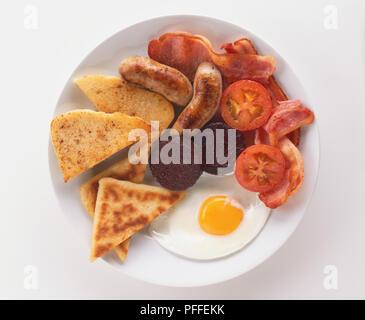 Ulster Fry, assiette petit-déjeuner y compris les saucisses, bacon, boudin noir, œuf frit, tomates et pain, vue de dessus. Banque D'Images