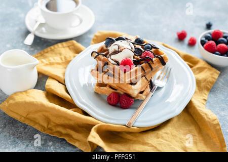 Gaufres Belges avec glace vanille et baies arrosées de chocolat et tasse de café sur l'arrière-plan. Selective focus Banque D'Images