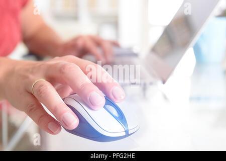 Femme travaillant au bureau à domicile à l'aide d'un ordinateur portable, souris d'ordinateur dans un avant-plan