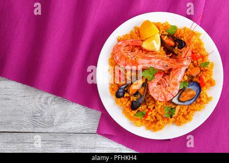 Partie de la paella de Valence de fruits de mer gastronomique avec des langoustines, des moules sur le riz et crémeuse salé avec des épices et des tranches de citron sur plaque, sur tapis de table Banque D'Images