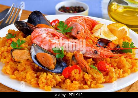 Partie de la paella de Valence de fruits de mer gastronomique avec des langoustines, des moules sur le riz et crémeuse salé avec des épices et des tranches de citron sur plaque, sur sol en bois cu Banque D'Images
