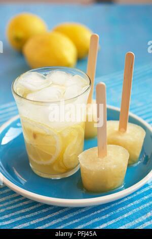 Verre de limonade et limonade trois sucettes glacées sur une assiette, avec les citrons frais dans le background, close-up Banque D'Images